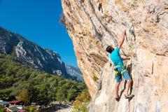 Ώριμος αρσενικός ορειβάτης που φθάνει στη λαβή στο φυσικό βράχο Στοκ εικόνες με δικαίωμα ελεύθερης χρήσης
