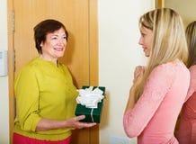 Ώριμος γείτονας που παρουσιάζει το δώρο στο νέο κορίτσι Στοκ Φωτογραφίες