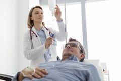 Ώριμος γιατρός που ρυθμίζει αλατούχο IV σταλαγματιά για τον ασθενή στο θάλαμο νοσοκομείων στοκ φωτογραφία με δικαίωμα ελεύθερης χρήσης