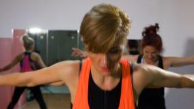 Ώριμος εκπαιδευτικός ικανότητας γυναικών που κάνει την ενεργητική σύνοδο αερόμπικ στη γυμναστική απόθεμα βίντεο