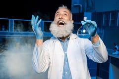 Ώριμος επιστήμονας στη φιάλη εκμετάλλευσης παλτών εργαστηρίων με το αντιδραστήριο στο εργαστήριο στοκ εικόνες
