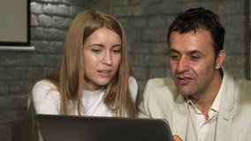Ώριμος επιχειρηματίας και ο νέος συνάδελφός του που εργάζονται στο lap-top απόθεμα βίντεο