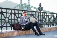 Ώριμος επιχειρηματίας με ένα lap-top σε μια πόλη Στοκ Φωτογραφία