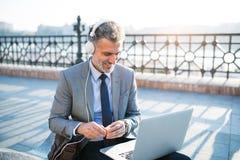 Ώριμος επιχειρηματίας με ένα lap-top σε μια πόλη Στοκ εικόνες με δικαίωμα ελεύθερης χρήσης