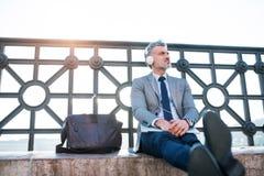 Ώριμος επιχειρηματίας με ένα lap-top σε μια πόλη Στοκ Εικόνες