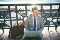 Ώριμος επιχειρηματίας με ένα lap-top σε μια πόλη Στοκ φωτογραφία με δικαίωμα ελεύθερης χρήσης