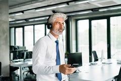 Ώριμος επιχειρηματίας με τα ακουστικά στο γραφείο Στοκ φωτογραφία με δικαίωμα ελεύθερης χρήσης