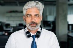Ώριμος επιχειρηματίας με τα ακουστικά στο γραφείο Στοκ Φωτογραφίες