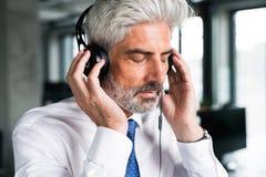 Ώριμος επιχειρηματίας με τα ακουστικά στο γραφείο Στοκ φωτογραφίες με δικαίωμα ελεύθερης χρήσης