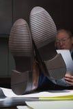 Ώριμος επιχειρηματίας με τα πόδια του επάνω στο γραφείο Στοκ Εικόνες
