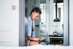 Ώριμος επιχειρηματίας με την ταμπλέτα σε ένα λουτρό δωματίου ξενοδοχείου Στοκ Φωτογραφίες