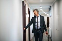 Ώριμος επιχειρηματίας με τις αποσκευές σε έναν διάδρομο ξενοδοχείων Στοκ Φωτογραφίες
