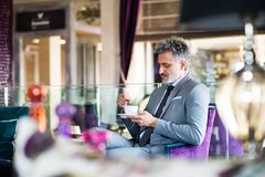 Ώριμος επιχειρηματίας με τον καφέ σε ένα σαλόνι ξενοδοχείων Στοκ εικόνα με δικαίωμα ελεύθερης χρήσης