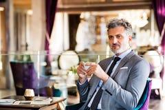 Ώριμος επιχειρηματίας με τον καφέ σε ένα σαλόνι ξενοδοχείων Στοκ Εικόνες