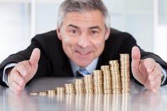 Ώριμος επιχειρηματίας με το σωρό των νομισμάτων Στοκ Φωτογραφίες