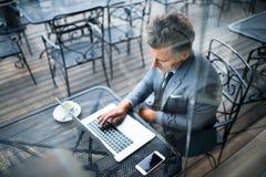 Ώριμος επιχειρηματίας με το lap-top έξω από έναν καφέ Στοκ εικόνα με δικαίωμα ελεύθερης χρήσης