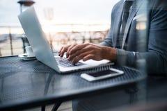 Ώριμος επιχειρηματίας με το lap-top έξω από έναν καφέ Στοκ Εικόνα