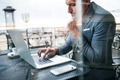 Ώριμος επιχειρηματίας με το lap-top έξω από έναν καφέ Στοκ φωτογραφίες με δικαίωμα ελεύθερης χρήσης