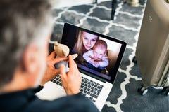 Ώριμος επιχειρηματίας με το lap-top σε ένα δωμάτιο ξενοδοχείου Στοκ Εικόνες