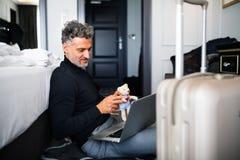 Ώριμος επιχειρηματίας με το lap-top σε ένα δωμάτιο ξενοδοχείου Στοκ Εικόνα