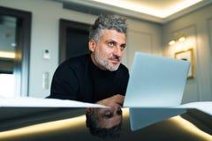Ώριμος επιχειρηματίας με το lap-top σε ένα δωμάτιο ξενοδοχείου Στοκ εικόνα με δικαίωμα ελεύθερης χρήσης