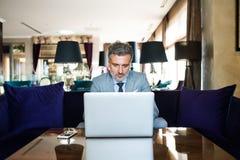 Ώριμος επιχειρηματίας με το lap-top σε ένα σαλόνι ξενοδοχείων Στοκ Φωτογραφίες