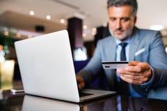 Ώριμος επιχειρηματίας με το lap-top σε ένα σαλόνι ξενοδοχείων Στοκ φωτογραφίες με δικαίωμα ελεύθερης χρήσης