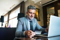 Ώριμος επιχειρηματίας με το lap-top σε ένα σαλόνι ξενοδοχείων Στοκ φωτογραφία με δικαίωμα ελεύθερης χρήσης