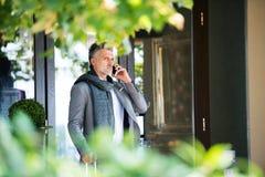 Ώριμος επιχειρηματίας με το smartphone μπροστά από ένα ξενοδοχείο Στοκ φωτογραφίες με δικαίωμα ελεύθερης χρήσης
