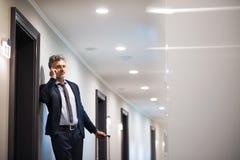 Ώριμος επιχειρηματίας με το smartphone σε έναν διάδρομο ξενοδοχείων Στοκ εικόνες με δικαίωμα ελεύθερης χρήσης