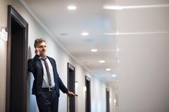 Ώριμος επιχειρηματίας με το smartphone σε έναν διάδρομο ξενοδοχείων Στοκ φωτογραφία με δικαίωμα ελεύθερης χρήσης