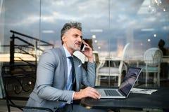 Ώριμος επιχειρηματίας με το smartphone σε έναν υπαίθριο καφέ ξενοδοχείων Στοκ φωτογραφία με δικαίωμα ελεύθερης χρήσης