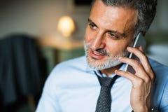 Ώριμος επιχειρηματίας με το smartphone σε ένα δωμάτιο ξενοδοχείου Στοκ φωτογραφία με δικαίωμα ελεύθερης χρήσης