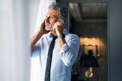 Ώριμος επιχειρηματίας με το smartphone σε ένα δωμάτιο ξενοδοχείου Στοκ Εικόνες
