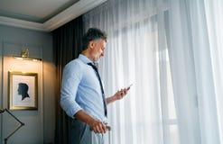 Ώριμος επιχειρηματίας με το smartphone σε ένα δωμάτιο ξενοδοχείου Στοκ Φωτογραφία