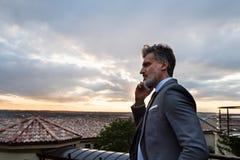 Ώριμος επιχειρηματίας με το smartphone σε ένα μπαλκόνι ξενοδοχείων Στοκ φωτογραφία με δικαίωμα ελεύθερης χρήσης