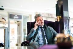 Ώριμος επιχειρηματίας με το smartphone σε ένα σαλόνι ξενοδοχείων Στοκ Εικόνα