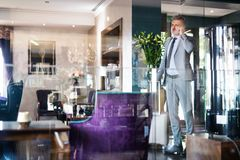 Ώριμος επιχειρηματίας με το smartphone σε ένα σαλόνι ξενοδοχείων Στοκ Φωτογραφία
