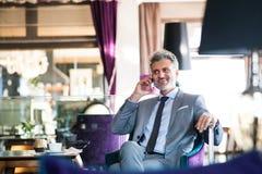 Ώριμος επιχειρηματίας με το smartphone σε ένα σαλόνι ξενοδοχείων Στοκ φωτογραφία με δικαίωμα ελεύθερης χρήσης