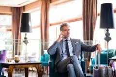 Ώριμος επιχειρηματίας με το smartphone σε ένα σαλόνι ξενοδοχείων Στοκ εικόνες με δικαίωμα ελεύθερης χρήσης