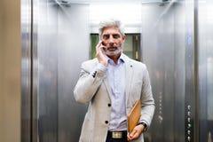 Ώριμος επιχειρηματίας με το smartphone στον ανελκυστήρα Στοκ φωτογραφία με δικαίωμα ελεύθερης χρήσης