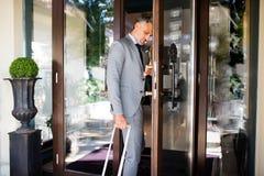 Ώριμος επιχειρηματίας που εισάγει το ξενοδοχείο με τις αποσκευές Στοκ Εικόνες