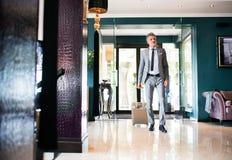 Ώριμος επιχειρηματίας που εισάγει το ξενοδοχείο με τις αποσκευές Στοκ φωτογραφία με δικαίωμα ελεύθερης χρήσης