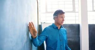 Ώριμος επιχειρηματίας που κάνει μια παρουσίαση πινάκων κιμωλίας σε ένα γραφείο Στοκ φωτογραφίες με δικαίωμα ελεύθερης χρήσης