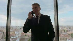 Ώριμος επιχειρηματίας που μιλά στο κινητό τηλέφωνο απόθεμα βίντεο