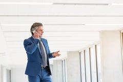 Ώριμος επιχειρηματίας που μιλά στο κινητό τηλέφωνο στο νέο γραφείο Στοκ Φωτογραφία