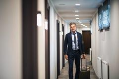 Ώριμος επιχειρηματίας που περπατά με τις αποσκευές σε έναν διάδρομο ξενοδοχείων Στοκ φωτογραφία με δικαίωμα ελεύθερης χρήσης