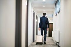 Ώριμος επιχειρηματίας που περπατά με τις αποσκευές σε έναν διάδρομο ξενοδοχείων Στοκ εικόνες με δικαίωμα ελεύθερης χρήσης