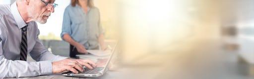 Ώριμος επιχειρηματίας που χρησιμοποιεί ένα lap-top, ελαφριά επίδραση Στοκ εικόνες με δικαίωμα ελεύθερης χρήσης