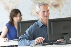 Ώριμος επιχειρηματίας που χρησιμοποιεί τον υπολογιστή στην αρχή Στοκ φωτογραφίες με δικαίωμα ελεύθερης χρήσης